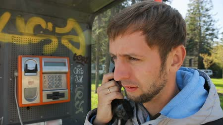 meio : Young guy taking off receiver of payphone, standing and holding phone at ear Stock Footage