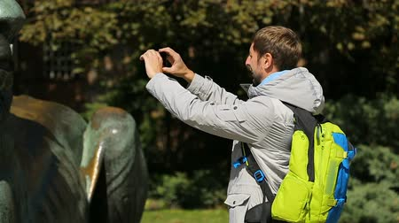 солдаты : Male tourist approaching lion monument, taking pictures with mobile phone camera