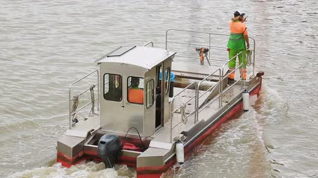 propelled : Self-propelled barge going down river, carrying workers and trash bin onboard Stock Footage