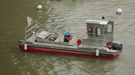 binário : Barge floating on river with trash can and scoop net aboard, municipal service