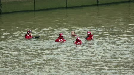 koers : Reddingsteam in rode jasjes, helmen zwemmen in water klaar voor training Stockvideo