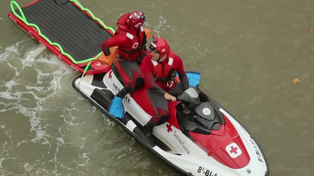 rescuer : Rescuers sitting on water motorcycle with water stretcher behind, first aid Stock Footage