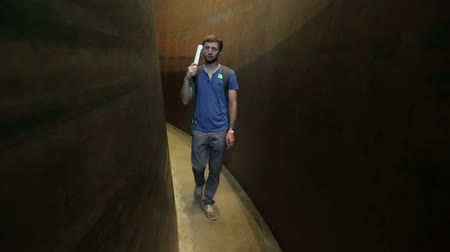 описание : Visitor walking down curved narrow passage between walls, listening audio guide