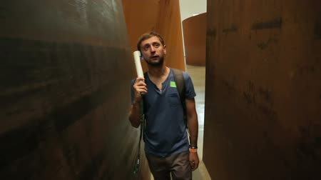 описание : Man walking through narrow passage between curved walls, listening to audio tour
