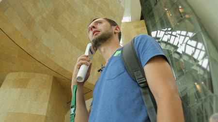 описание : Male tourist choosing and listening to his audio guide in museum, sightseeing