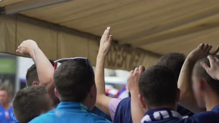 fan zone : Male supporters from France cheering and watching football match in fan-zone
