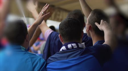 crowd together : Men shouting football slogan and raising hands at sport competition, supporters Stock Footage