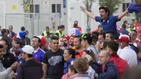плечо : Happy French fan sitting on friends shoulders and shouting, outdoor fan-zone