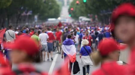crowd together : Excited football fans walking in the street with flags, outdoor fan-zone Stock Footage