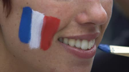 üç renkli : Close up of smiling woman face painting flag of France on cheeks, make-up