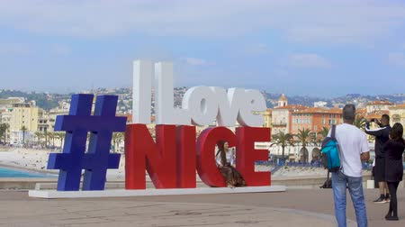 francouzština : Foreign tourists making photos near big memorial inscription about love to Nice
