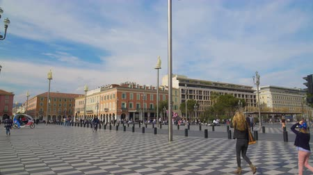 main : Pedestrians walking along historic and main square in Nice, Place Massena Stock Footage