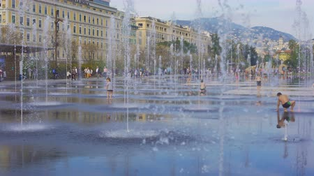 joyfulness : Happy curious children running and playing between trickles of mirror fountain
