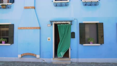 arrumado : Beautiful view on tidy blue house with flowerpots on windows, Burano, Venice