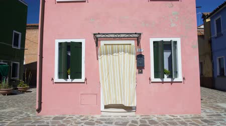 burano : View on beautiful pink house with flowerpots and curtain on door in Burano