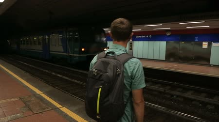 meio : Man standing on subway platform, train passing station, public transportation