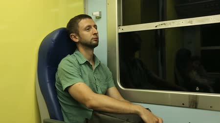 meio : Exhausted male traveler sitting in his seat going to another city by night train