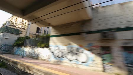 meio : City train going through passageway with graffiti walls and buildings in Naples
