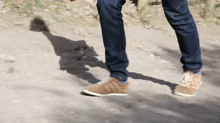 montanhoso : Teenager going up hilly ground road with shadow cast aside, male legs walking Stock Footage