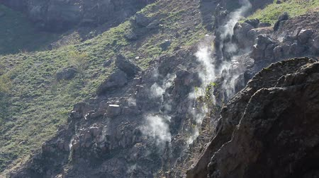 sulfur : White steam rising up from under stones on rocky slopes sunny day, volcano