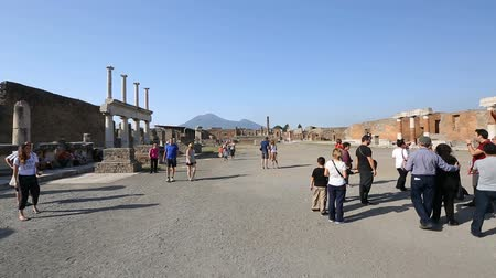 vyhlídkové : Group tourists standing on spacious square in Pompeii, Temple of Jupiter at back