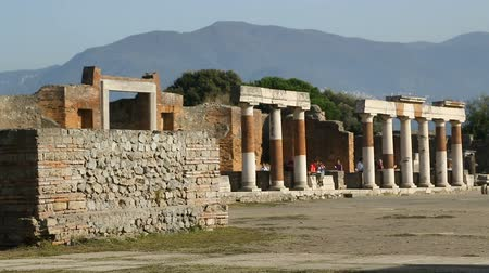 konzervált : Broken row of ancient columns lining up square in Pompeii, people walking behind Stock mozgókép
