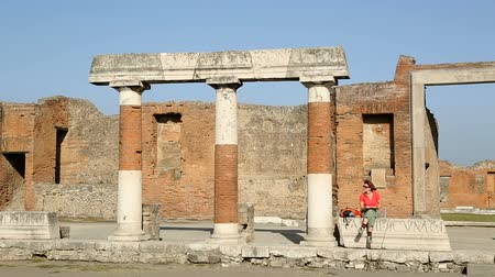 építészeti : Female sitting on entablature with row of columns, tourists walking on square