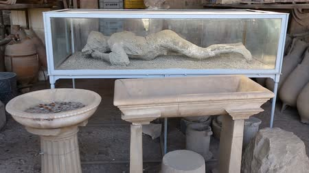 konzervace : Vesuvius eruption victim in plaster cast lying in glass showcase in Pompeii city
