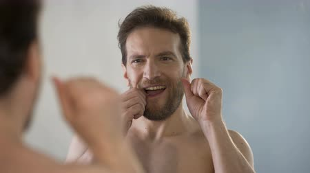 üstsüz : Guy taking care of oral hygiene, brushing his teeth with dental floss every day