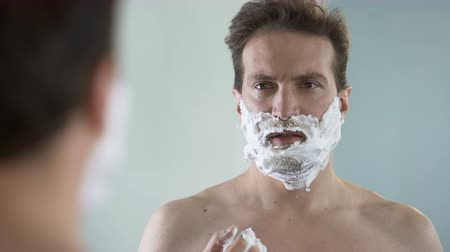 shaving foam : Man preparing to shave, feeling discomfort and tingle on face from shaving foam Stock Footage