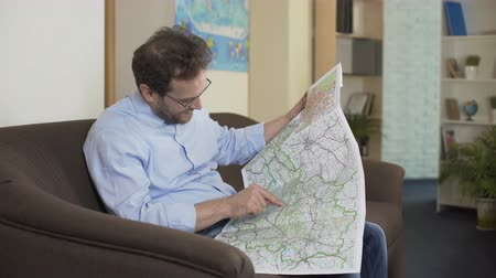 point of interest : Joyful man sitting on sofa and choosing resort city on map, adventurer Stock Footage