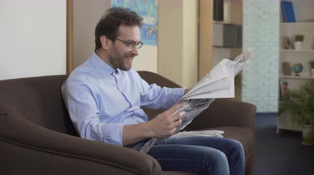 tényleges : Satisfied principal reading newspaper, relaxed person sitting on sofa, press