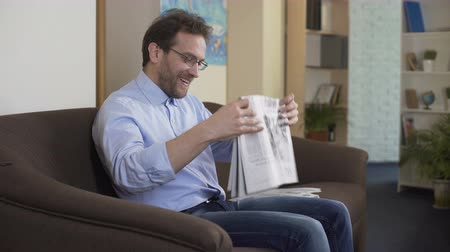 tényleges : Joyful man reading horoscope in newspaper and enjoying life, weekend at home