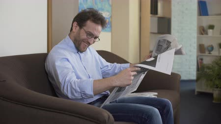 semanal : Pleased man reading anecdotes in newspaper, free time and relaxation at home