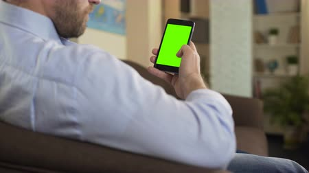 сороковые годы : Confident male reading political news on smartphone with green screen, app
