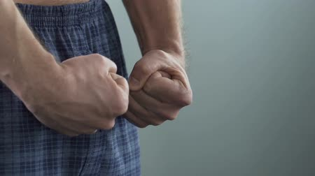 дополнительный : View on male clenching his fists, mans strength and health, potency. Close-up Стоковые видеозаписи