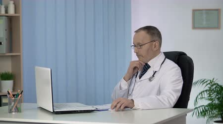 a medicare : Doctor conducting online consultations pondering on difficult case of patient