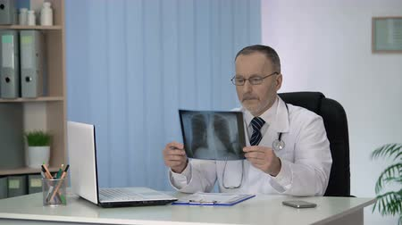 опытный : Experienced radiologist carefully examining and describing X-ray image of lungs