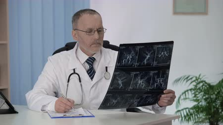 описание : Neurologist checking angiography of blood vessels, making description in cards Стоковые видеозаписи