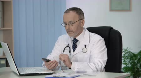 описание : Doctor reading medical reference book in special application on his smartphone Стоковые видеозаписи