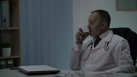 kötelesség : Surgeon relaxing after hard operation drinking alcohol and pondering his actions