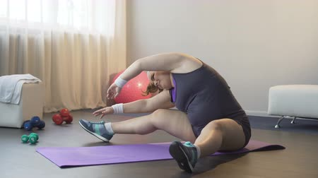 willpower : Plump girl gathering strength and getting down to difficult stretching exercises