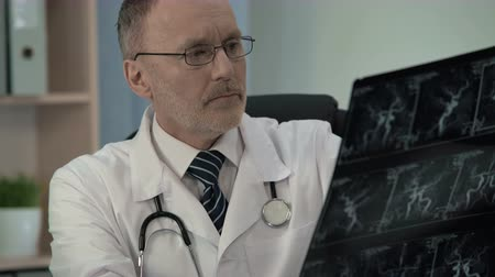 blood circulation : Neurologist examining patient venogram and typing his findings in patient card Stock Footage