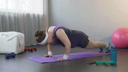 bodyweight : Obese girl with weak arm muscles trying to do push-ups, weight loss workout