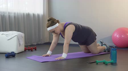 willpower : Obese young woman pushing up and falling on floor, working hard to lose weight