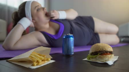 roliço : Lazy lady in sportswear lying on yoga mat eating junk food instead of training Vídeos