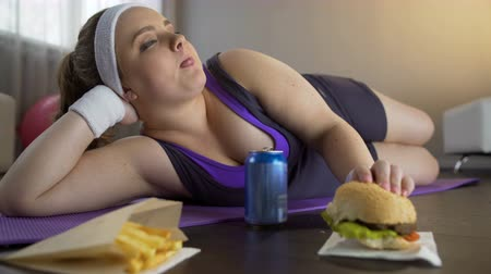 telített : Happy self-confident obese girl eating greasy burger instead of sports workout Stock mozgókép