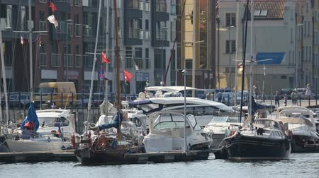парусное судно : Beautiful white yachts with waving flags parked in Gdansk port, water transport