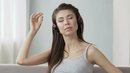 tense : Young woman in headphones listening to music and stretching neck, healthcare Stock Footage