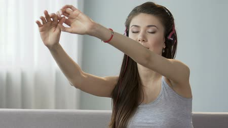gravado : Pretty female in headphones stretching back, audio guide to physical exercises Stock Footage
